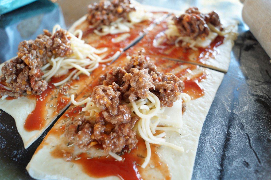 Små indbagte pizzaer med spaghetti og kødsovs
